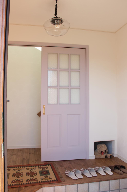 玄関を開けるとパープルの無垢ドアが目に飛び込んできます